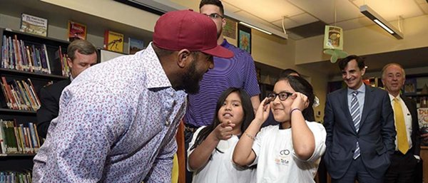 Former Baltimore Ravens lineback Ray Lewis hands out glasses to students at Vision for Baltimore launch May 9, 2016